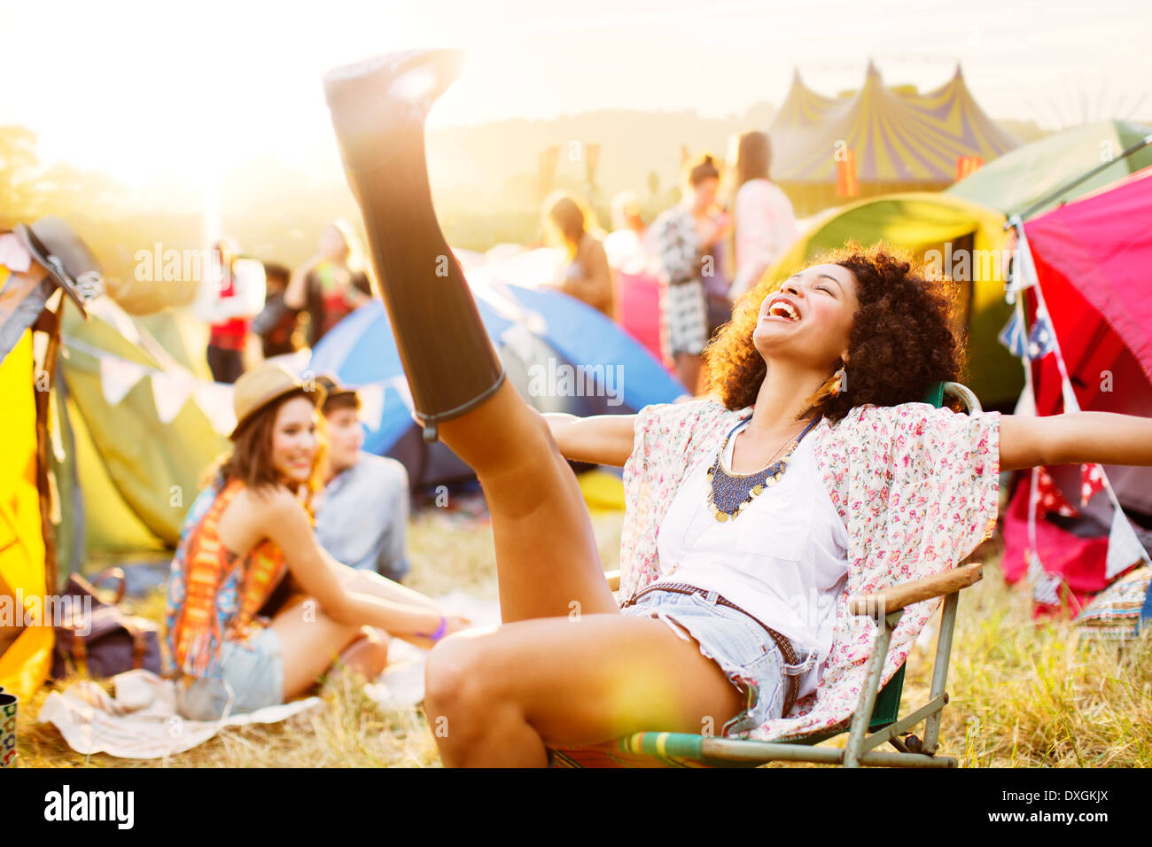 Carefree woman outside tents at music festival Stock Photo