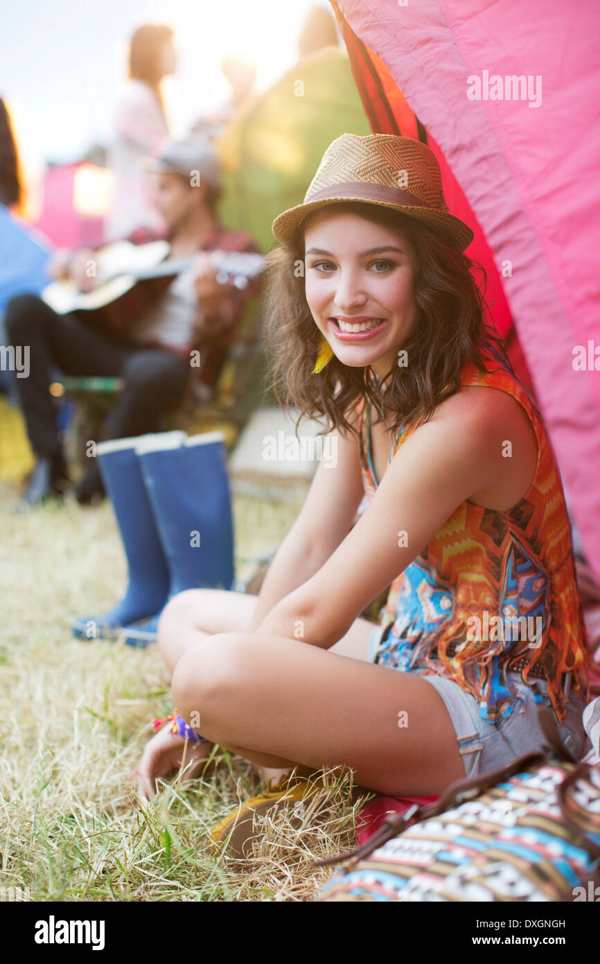 Portrait of smiling woman sitting at tent at music festival - Stock Image