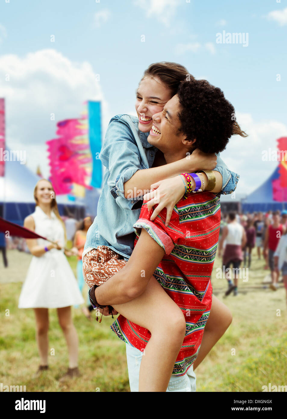 Enthusiastic couple hugging at music festival - Stock Image