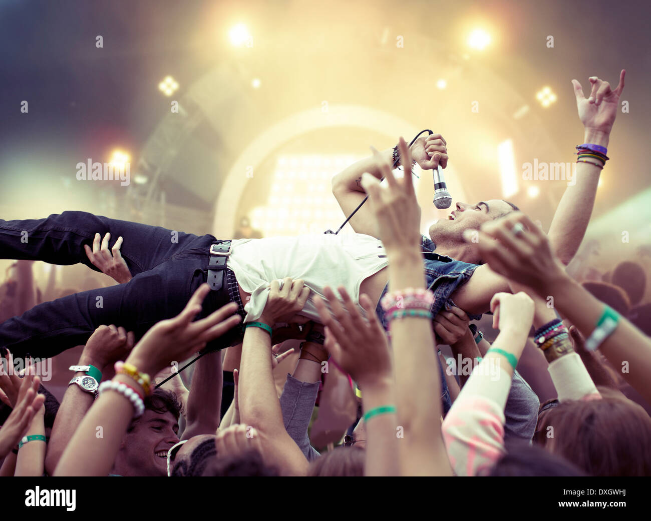 Performer crowd surfing at music festival - Stock Image