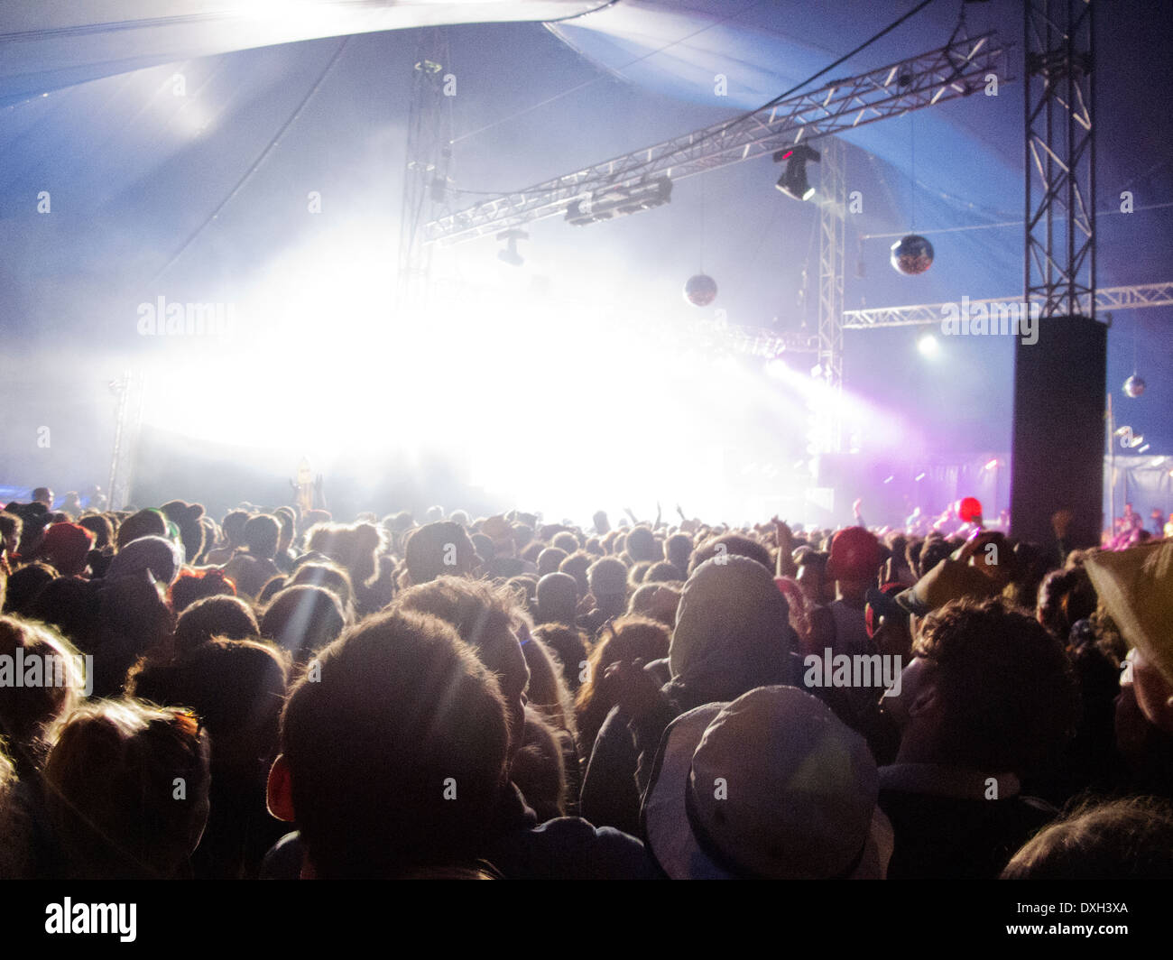 Fans facing illuminated stage at music festival - Stock Image