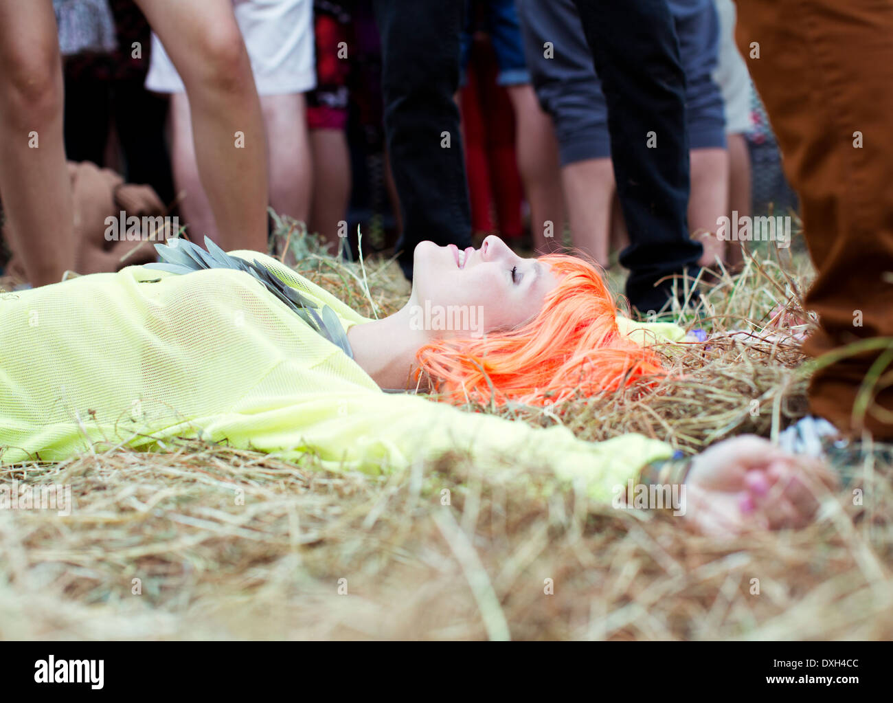Woman in wig laying with arms outstretched in grass at music festival Stock Photo