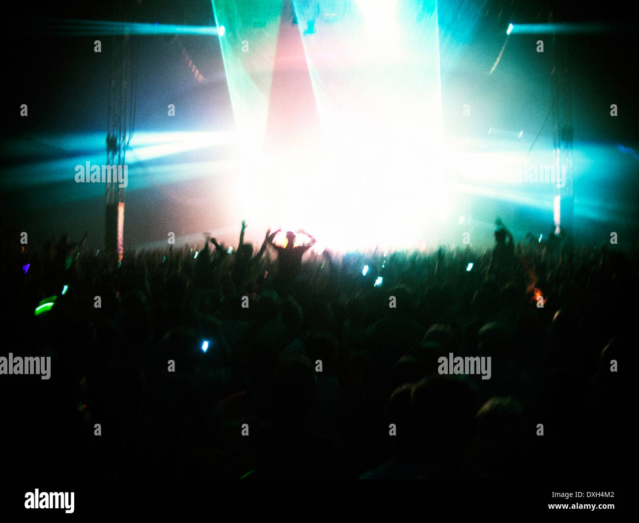 Fans facing illuminated stage - Stock Image