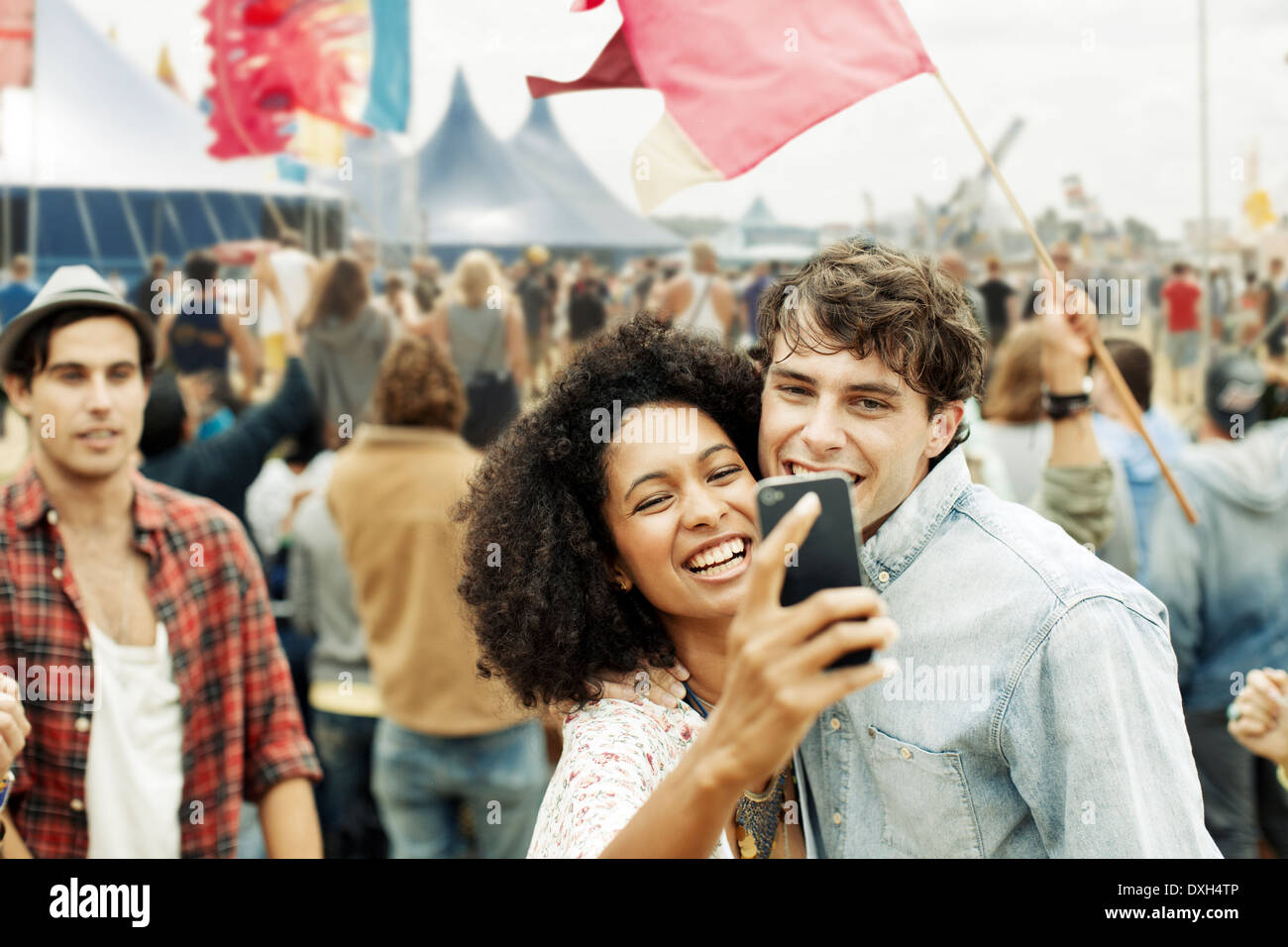 Couple taking self-portrait with camera phone at music festival - Stock Image