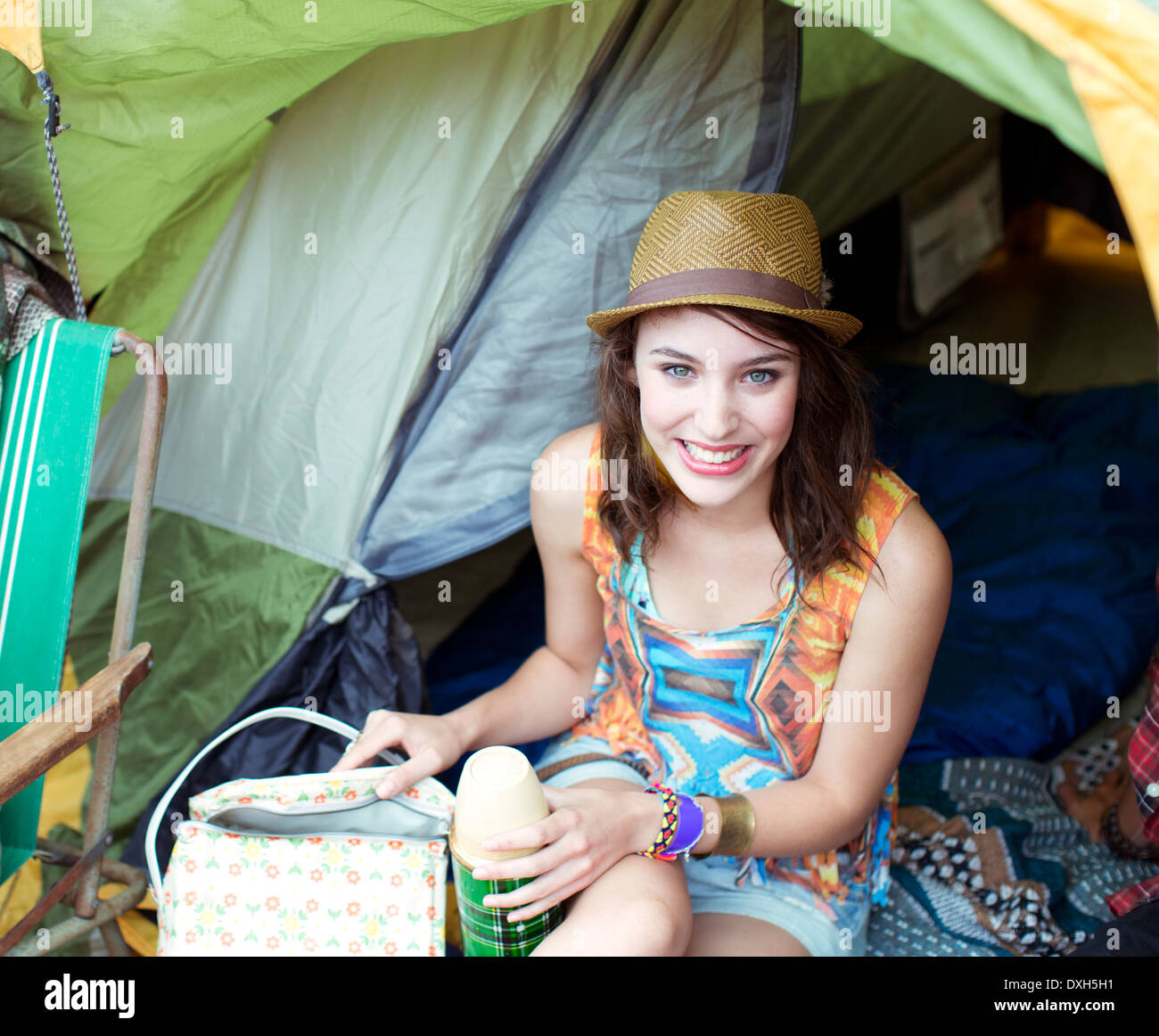 Portrait of smiling woman in tent at music festival - Stock Image