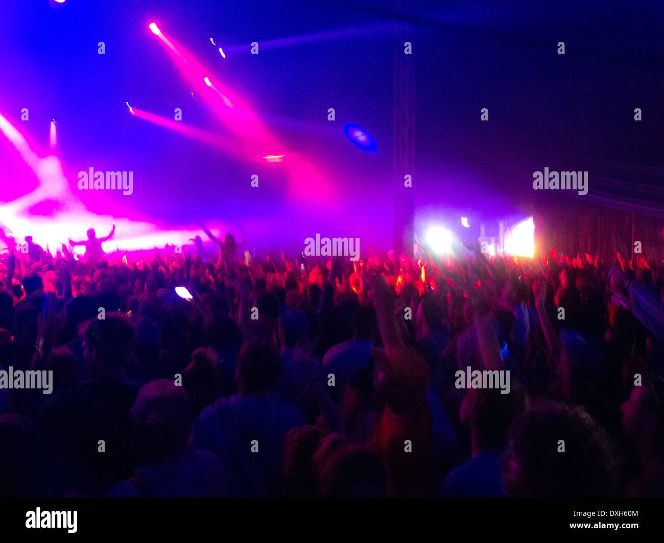 Crowd facing illuminated stage - Stock Image