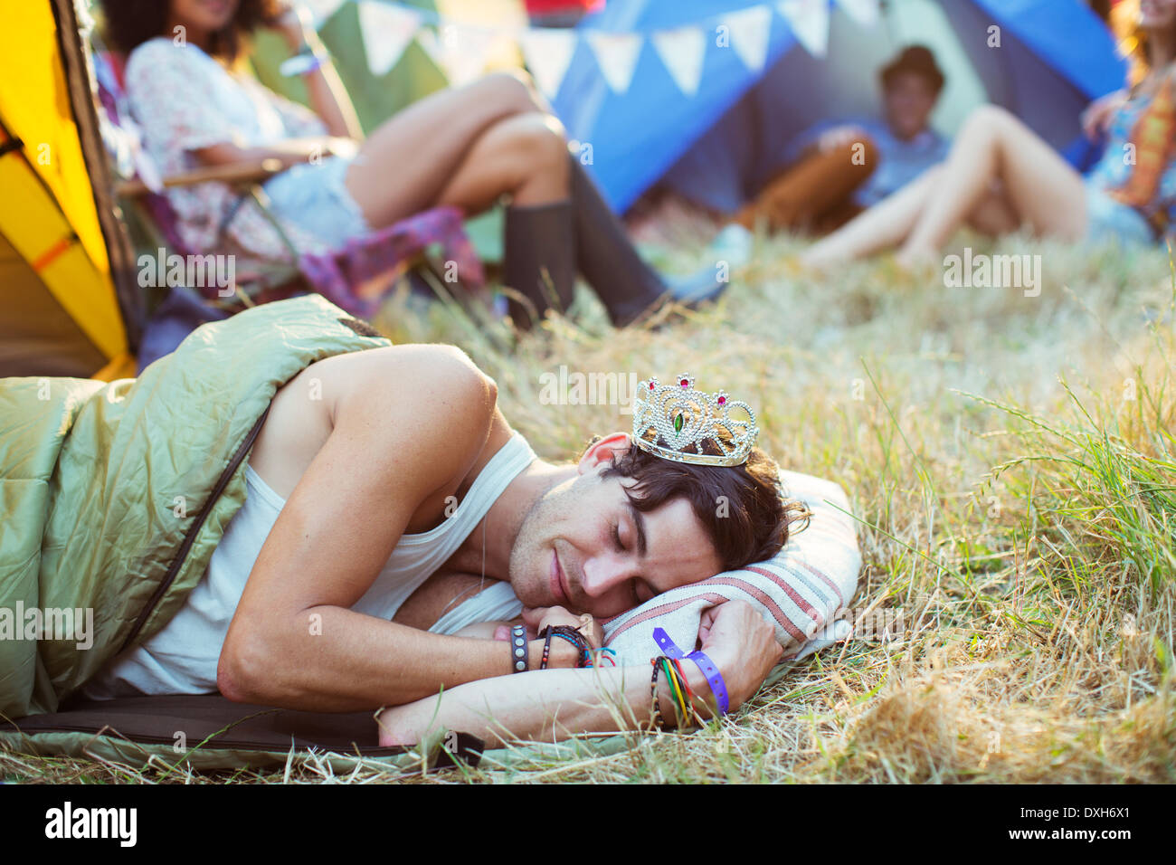 Man in tiara sleeping in sleeping bag outside tents at music festival - Stock Image