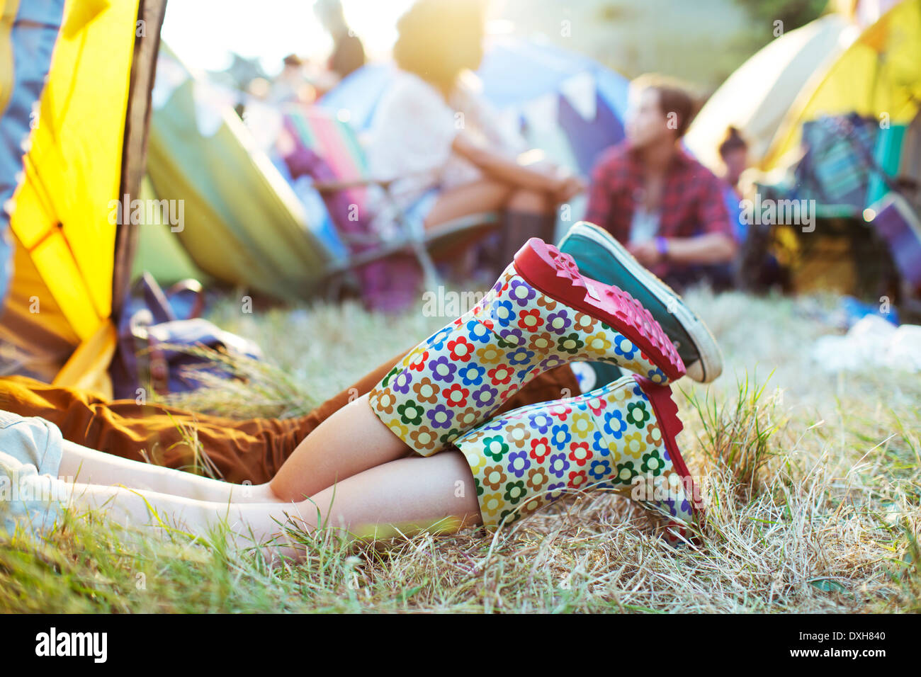 CoupleÍs legs sticking out of tent at music festival - Stock Image
