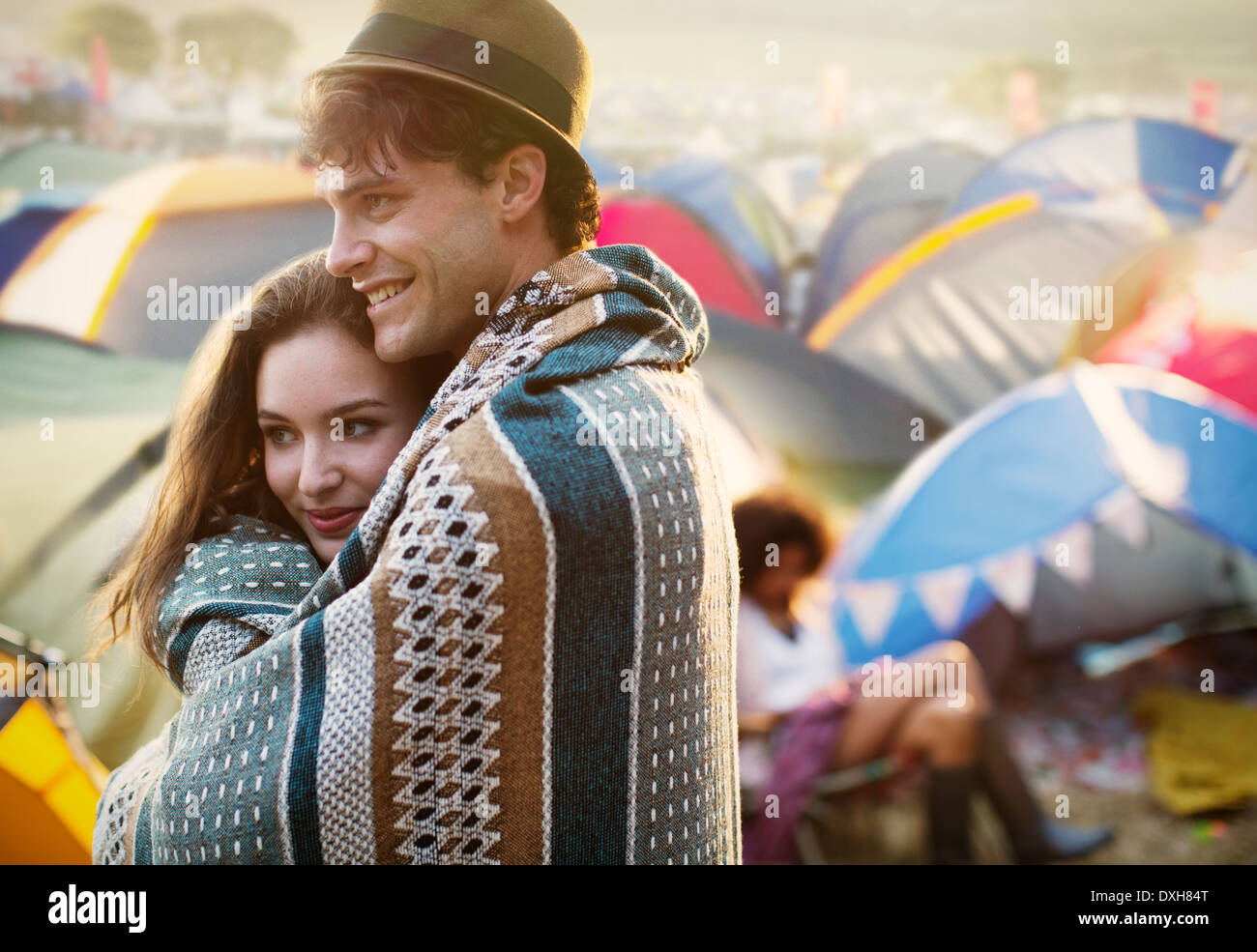 Couple wrapped in a blanket outside tents at music festival - Stock Image