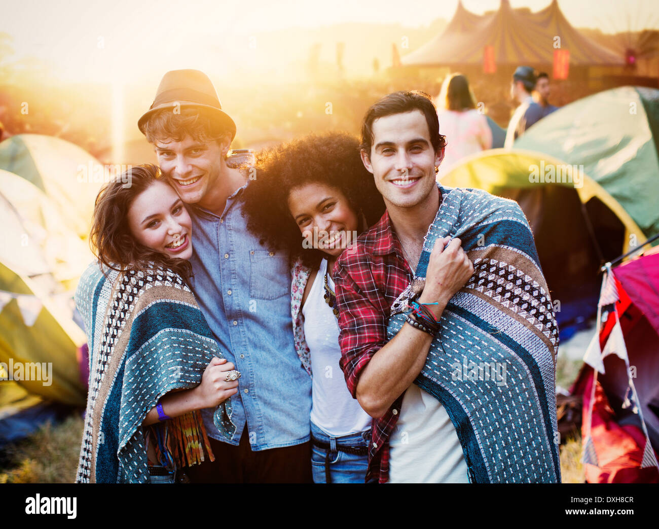Portrait of couples wrapped in a blanket outside tents at music festival - Stock Image