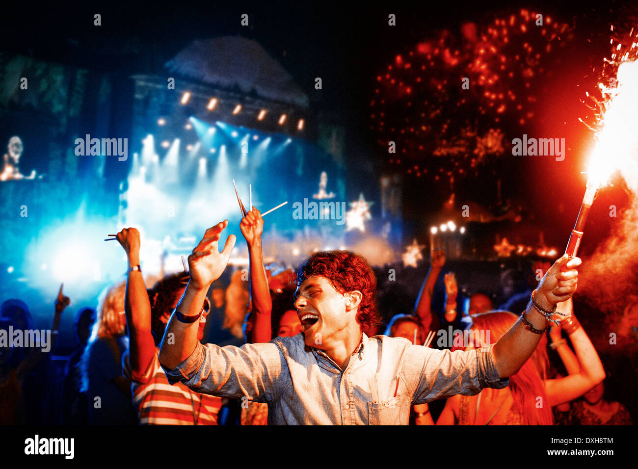 Fans with fireworks at music festival - Stock Image