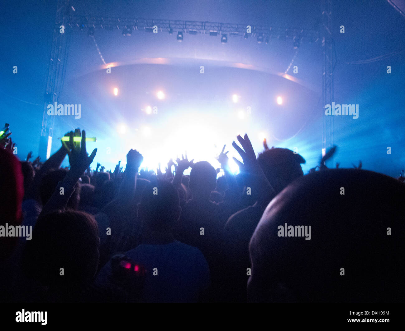 Silhouette of crowd facing stage at music festival - Stock Image