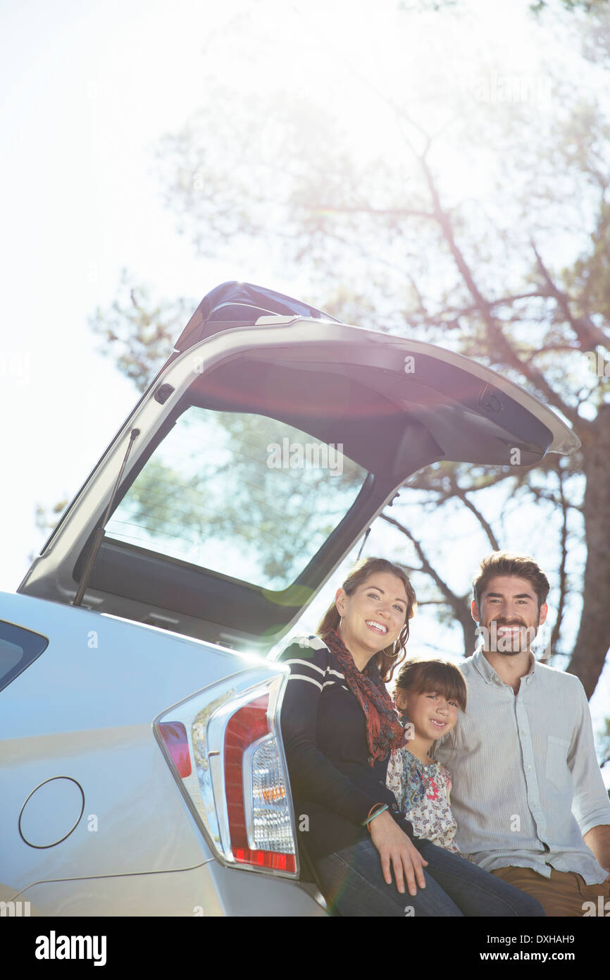 Portrait of smiling family sitting against rear of car - Stock Image