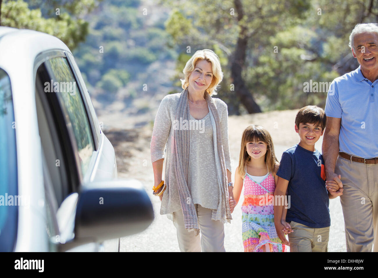 Grandparents and grandchildren holding hands outside car - Stock Image