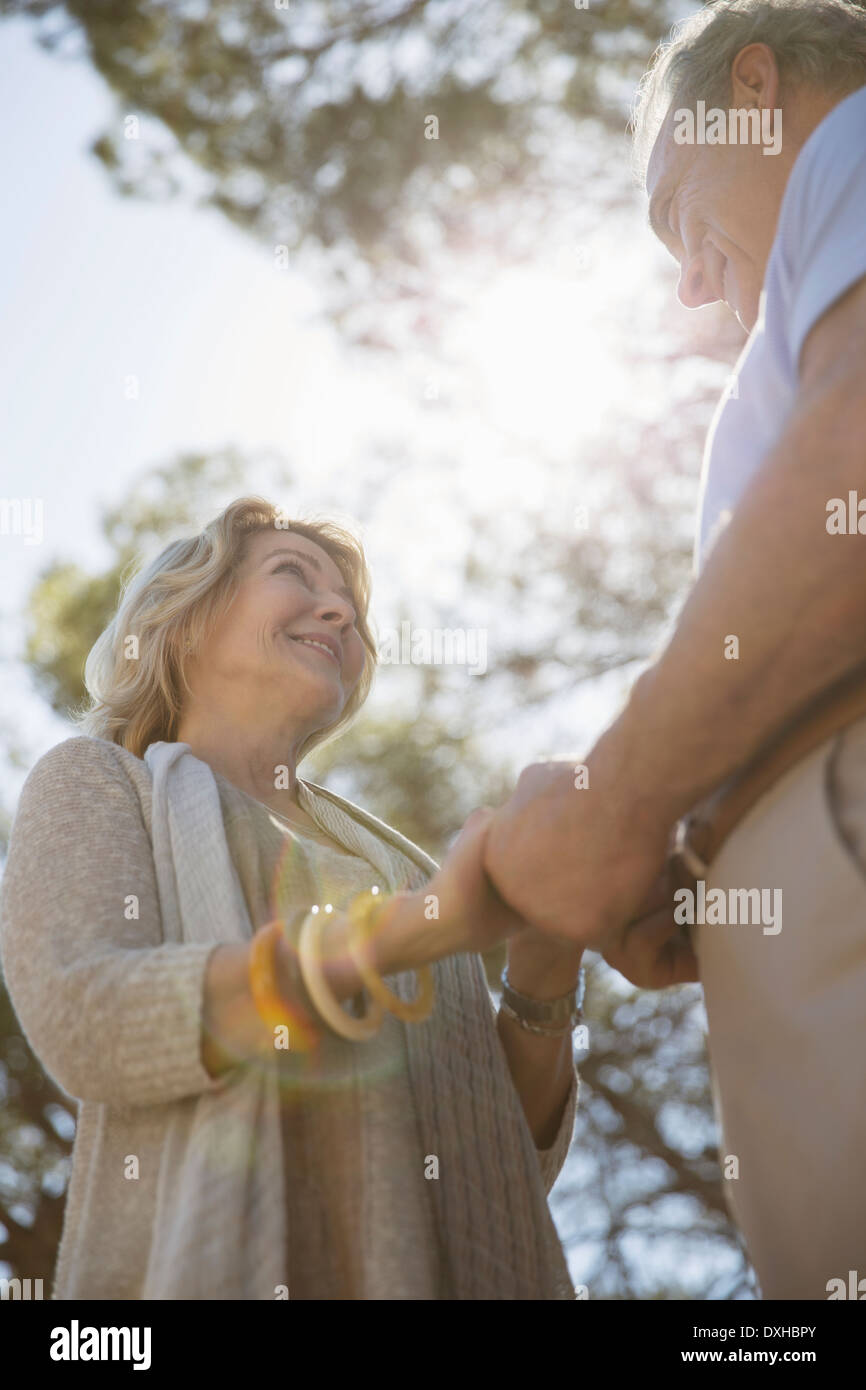 Senior couple holding hands under trees - Stock Image