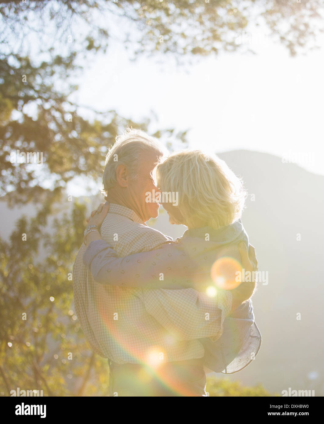 Senior man carrying woman outdoors - Stock Image