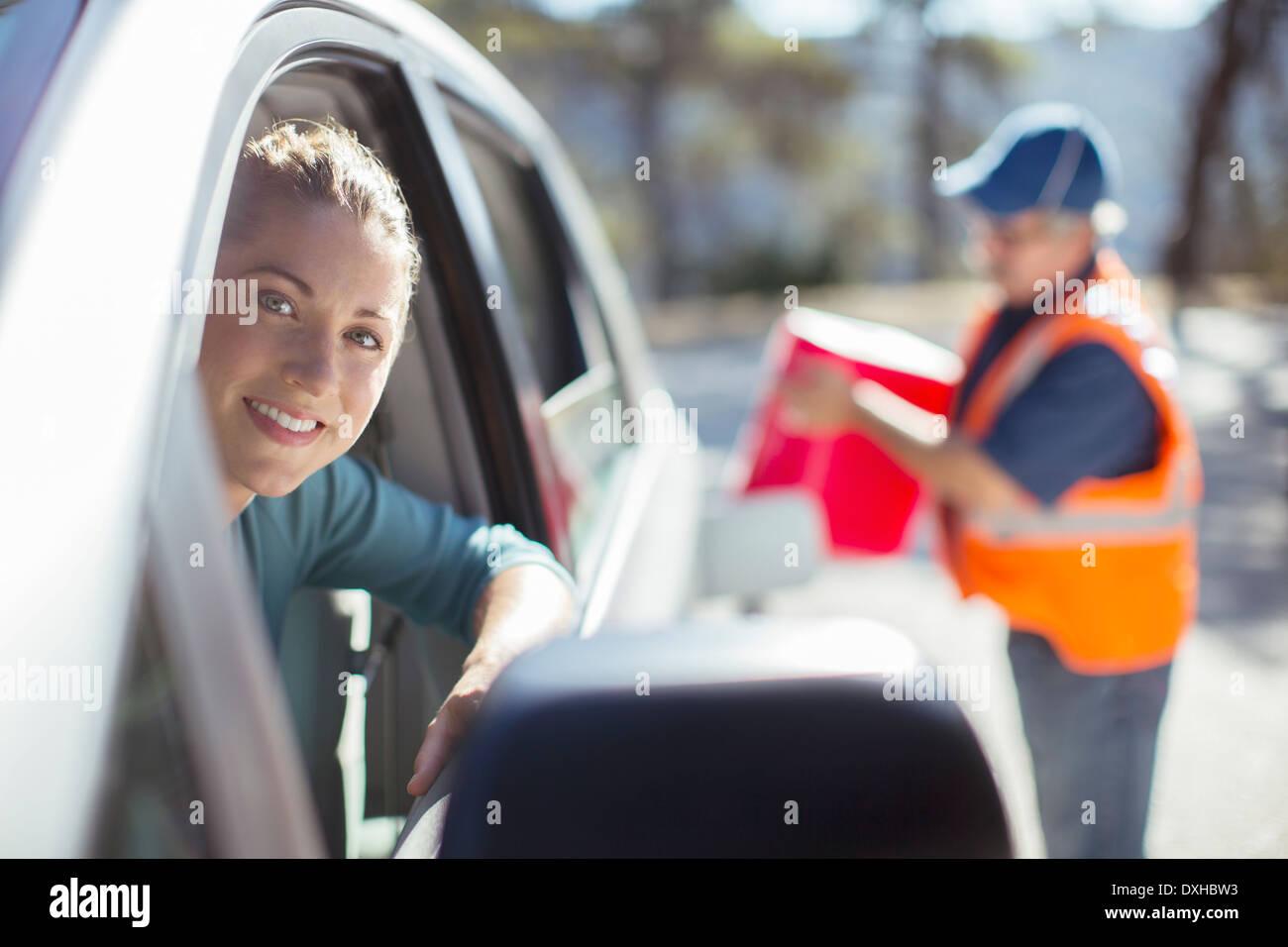Roadside mechanic filling gas tank for woman - Stock Image