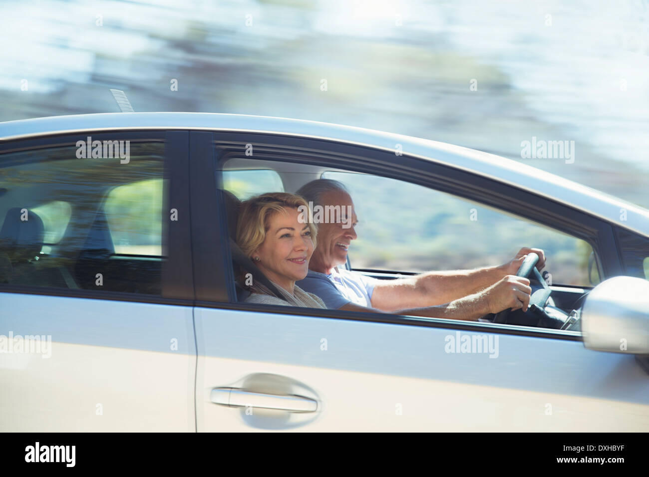 Happy senior couple driving in car - Stock Image