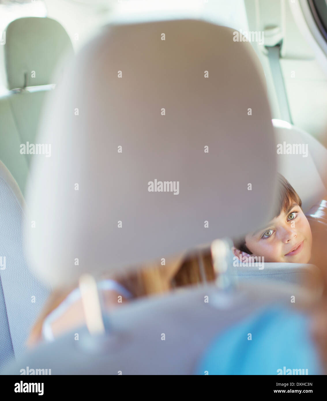 Mother turning to talk to children in back seat of car - Stock Image