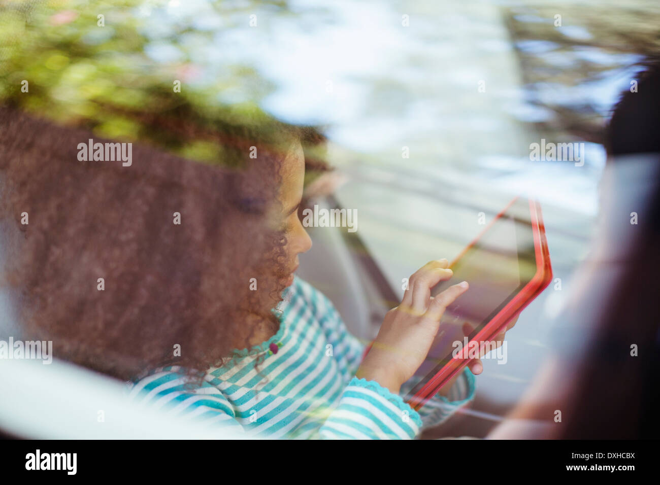 Girl using digital tablet in back seat of car - Stock Image