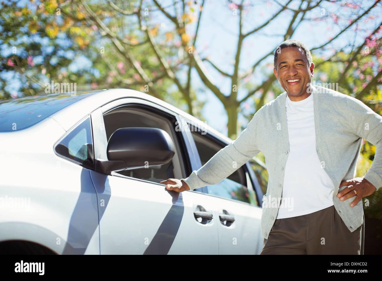 Portrait of confident senior man leaning against car - Stock Image