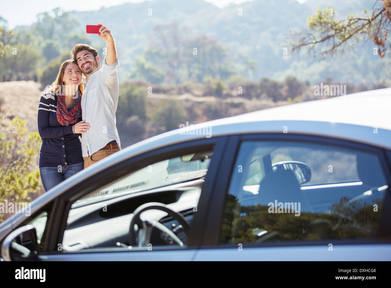Couple Taking Self Portrait With Cell Phone Outside Car Stock Photo Alamy