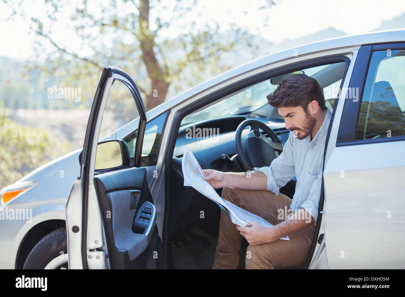 Man in car looking at map - Stock Image