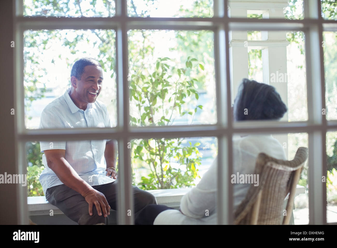 Happy senior couple talking on porch - Stock Image
