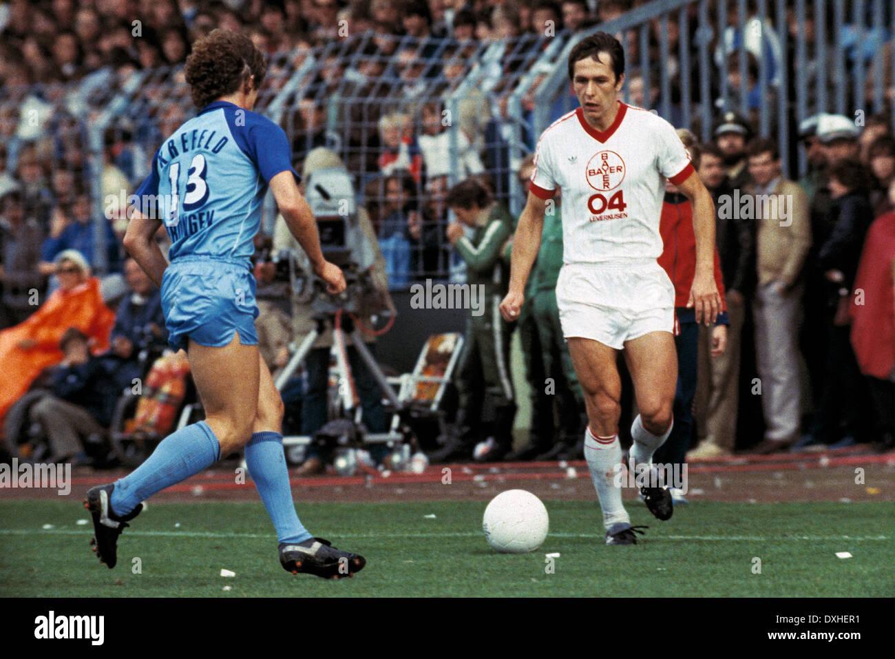 football, Bundesliga, 1983/1984, Grotenburg Stadium, FC Bayer 05 Uerdingen versus Bayer 04 Leverkusen 2:1, scene of the match, Rudolf Wojtowicz (Leverkusen) in ball possession, left Norbert Hofmann (Uerdingen) - Stock Image