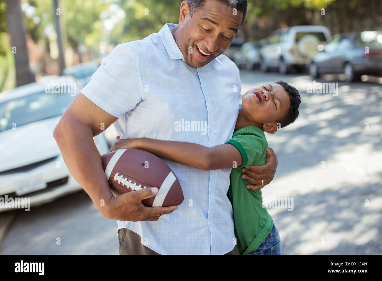 Grandson tackling grandfather with football - Stock Image