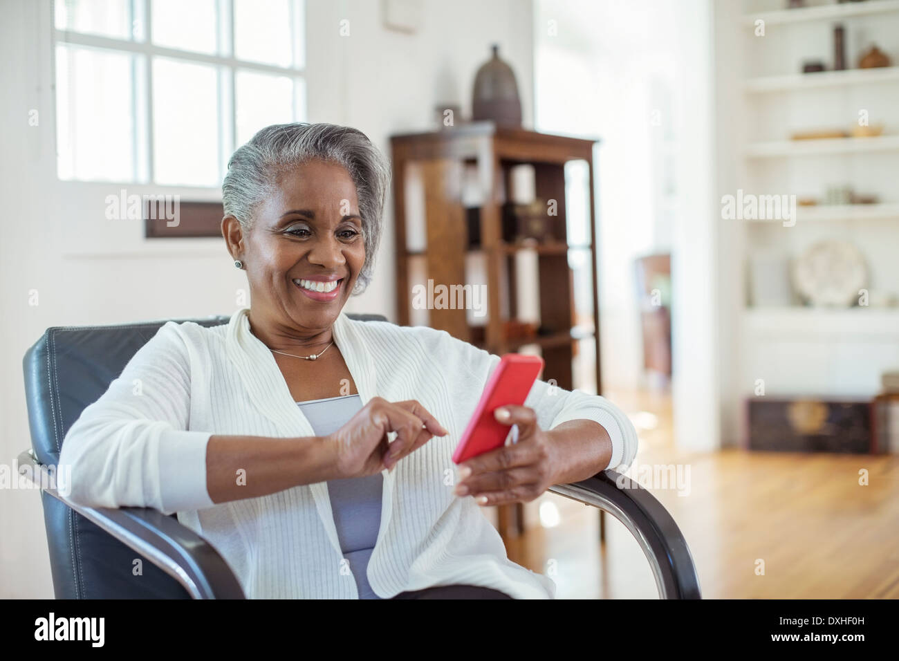 Happy senior woman text messaging with cell phone in living room - Stock Image