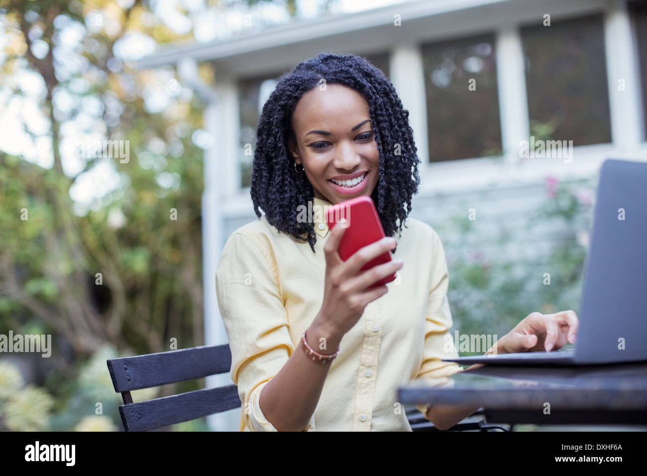 Smiling woman using cell phone and laptop on patio - Stock Image