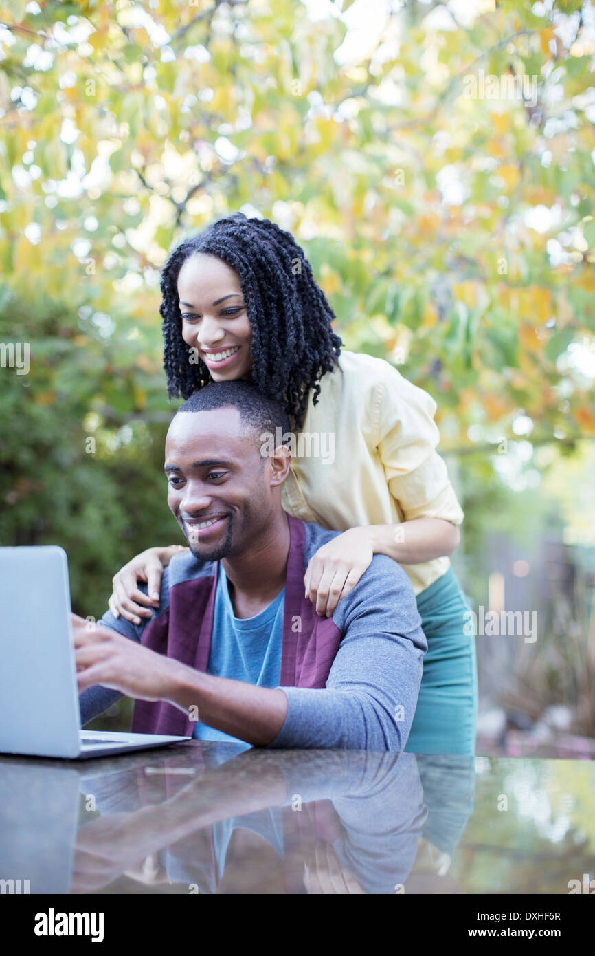 Happy couple using laptop at patio table - Stock Image