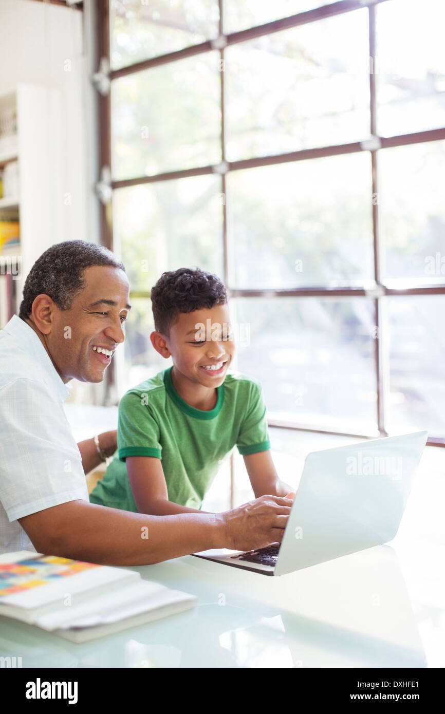 Grandfather and grandson using laptop - Stock Image