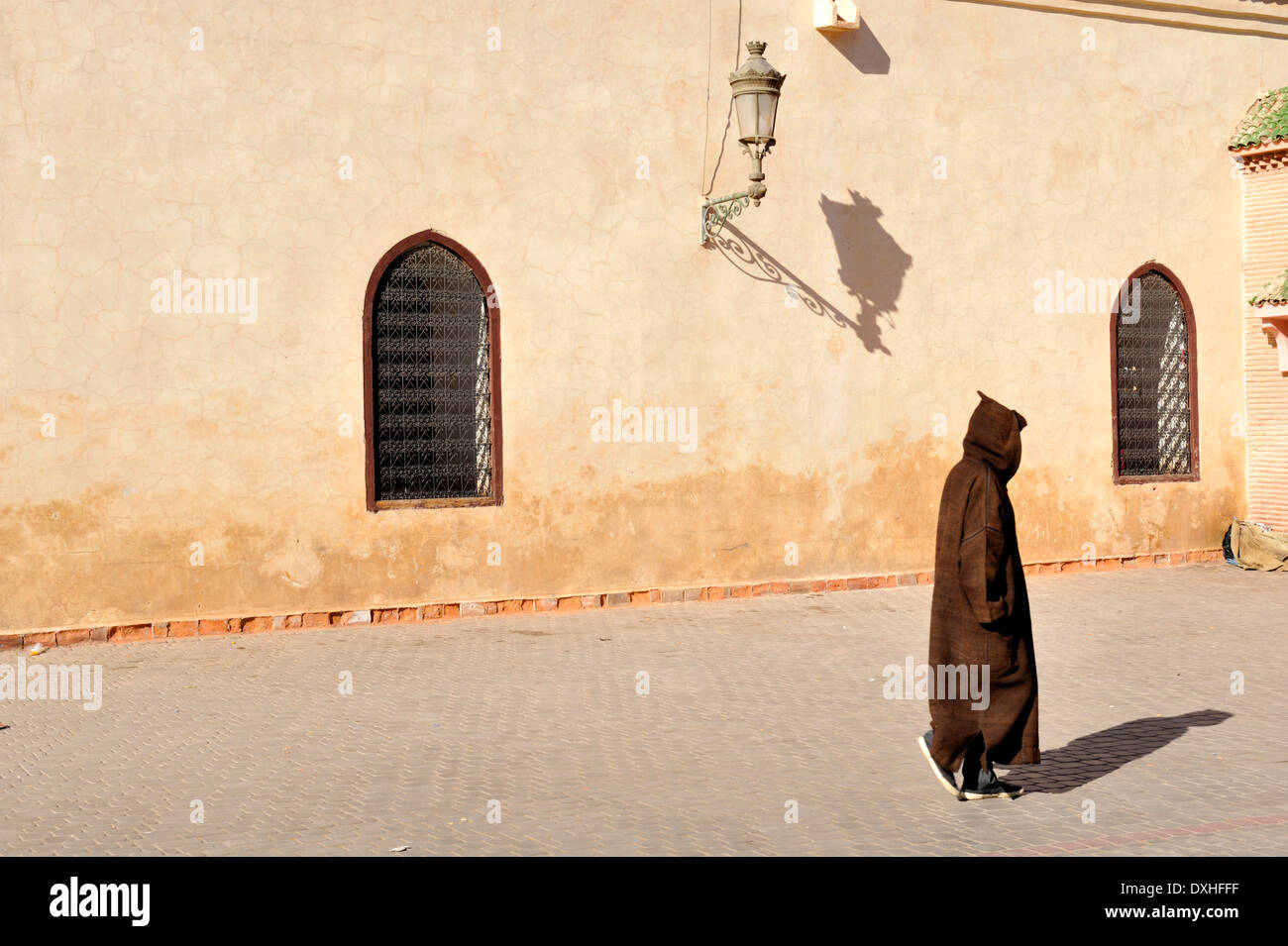 Berber, Moroccan, man in traditional hooded robe walking by wall, Marrakech, Morocco - Stock Image