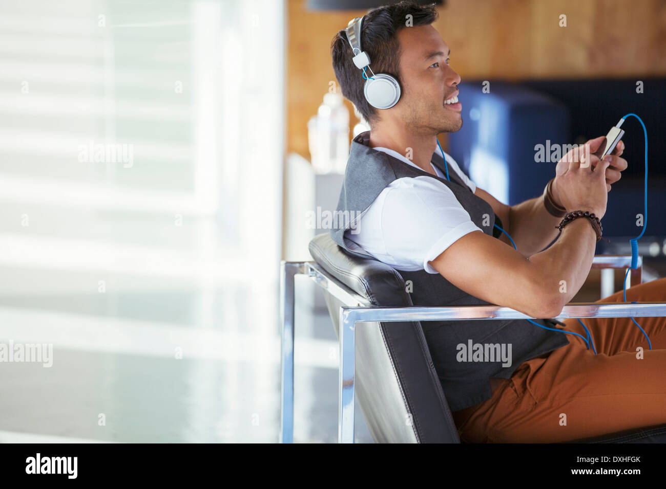 Smiling businessman listening to music on mp3 player with headphones - Stock Image