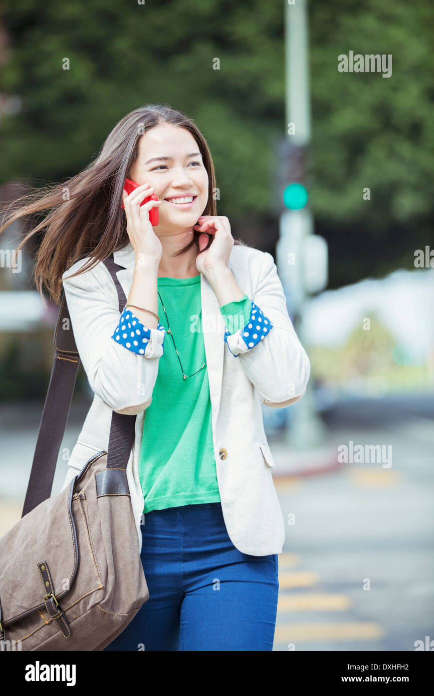 Happy businesswoman talking on cell phone in crosswalk - Stock Image