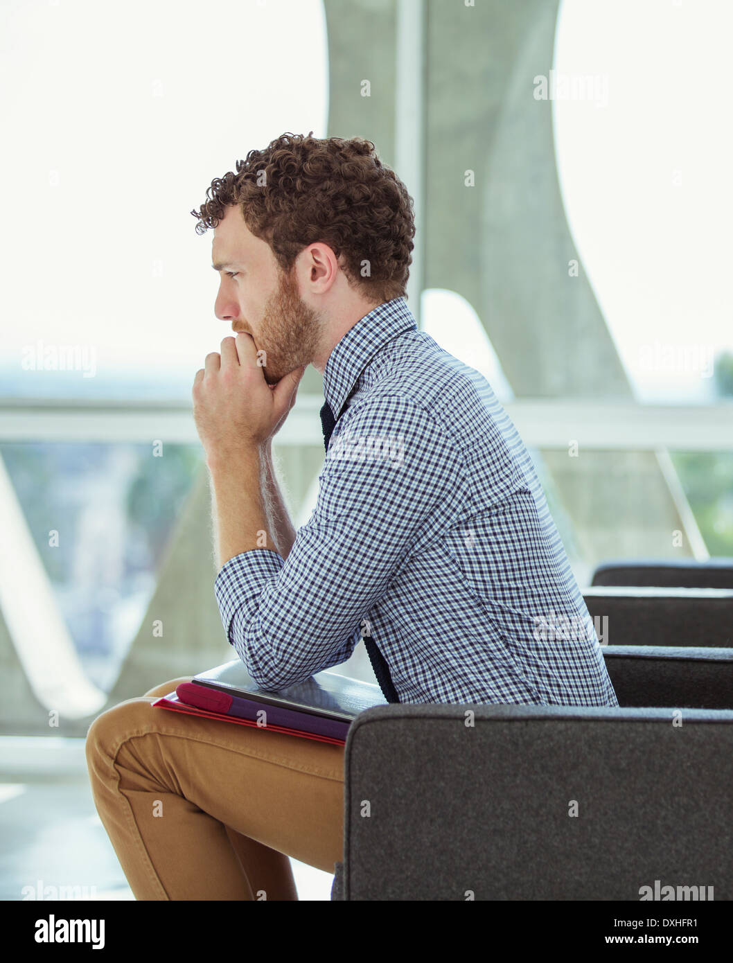 Pensive businessman sitting in office lobby - Stock Image