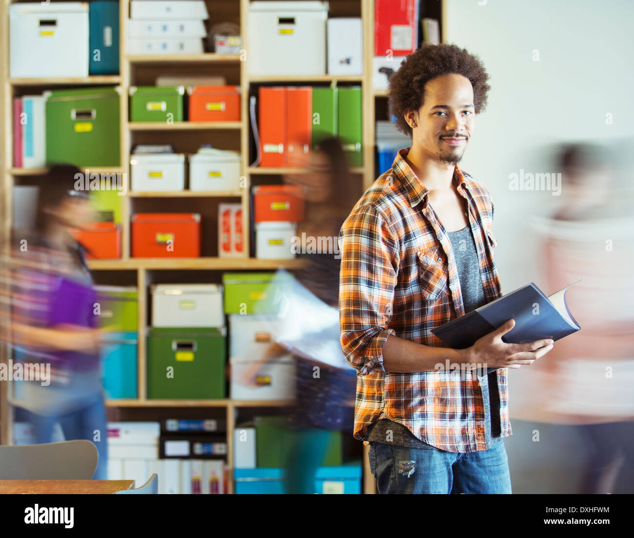Portrait of casual businessman with co-workers rushing by in background - Stock Image