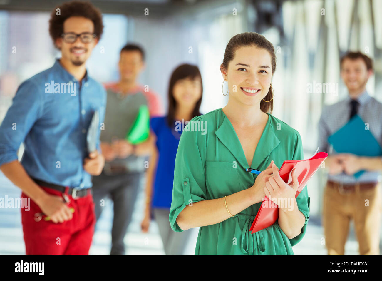 Portrait of creative businesswoman with folder and co-workers in corridor - Stock Image