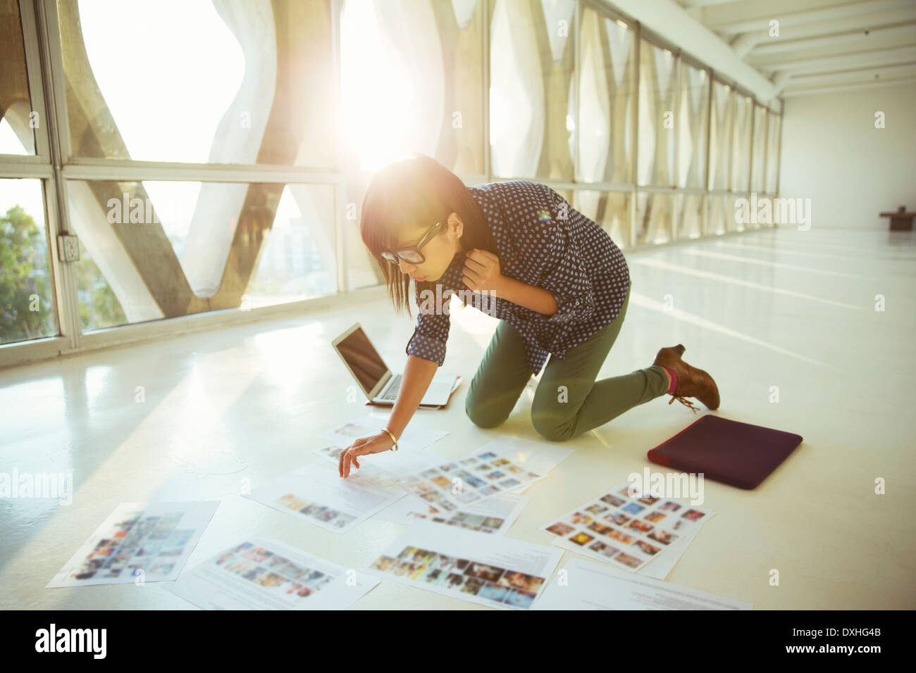 Creative businesswoman reviewing photography proofs on office floor - Stock Image