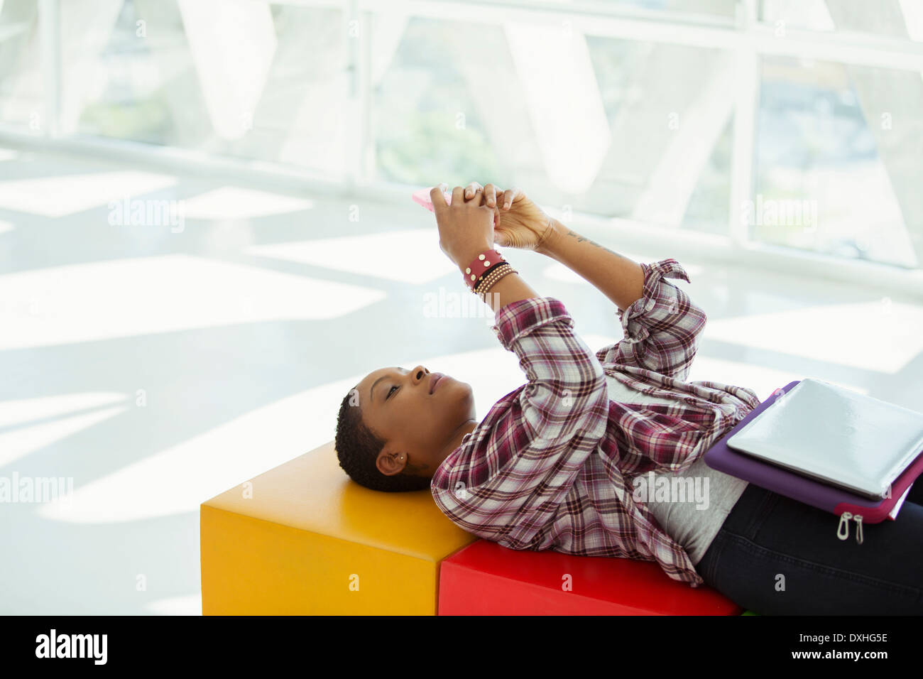 Casual businesswoman laying on bench and text messaging with cell phone - Stock Image