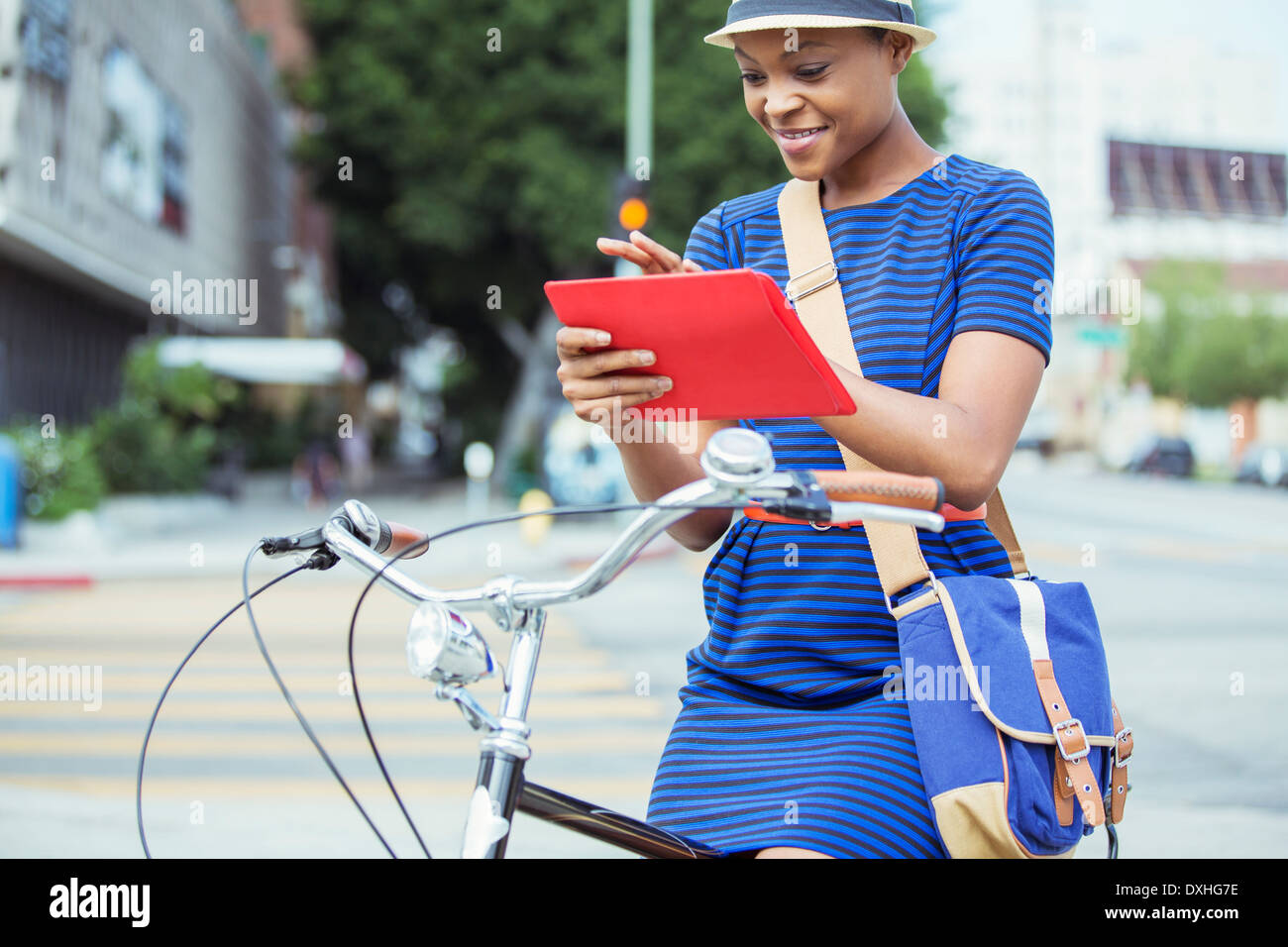Casual businesswoman using digital tablet on bicycle on urban street - Stock Image