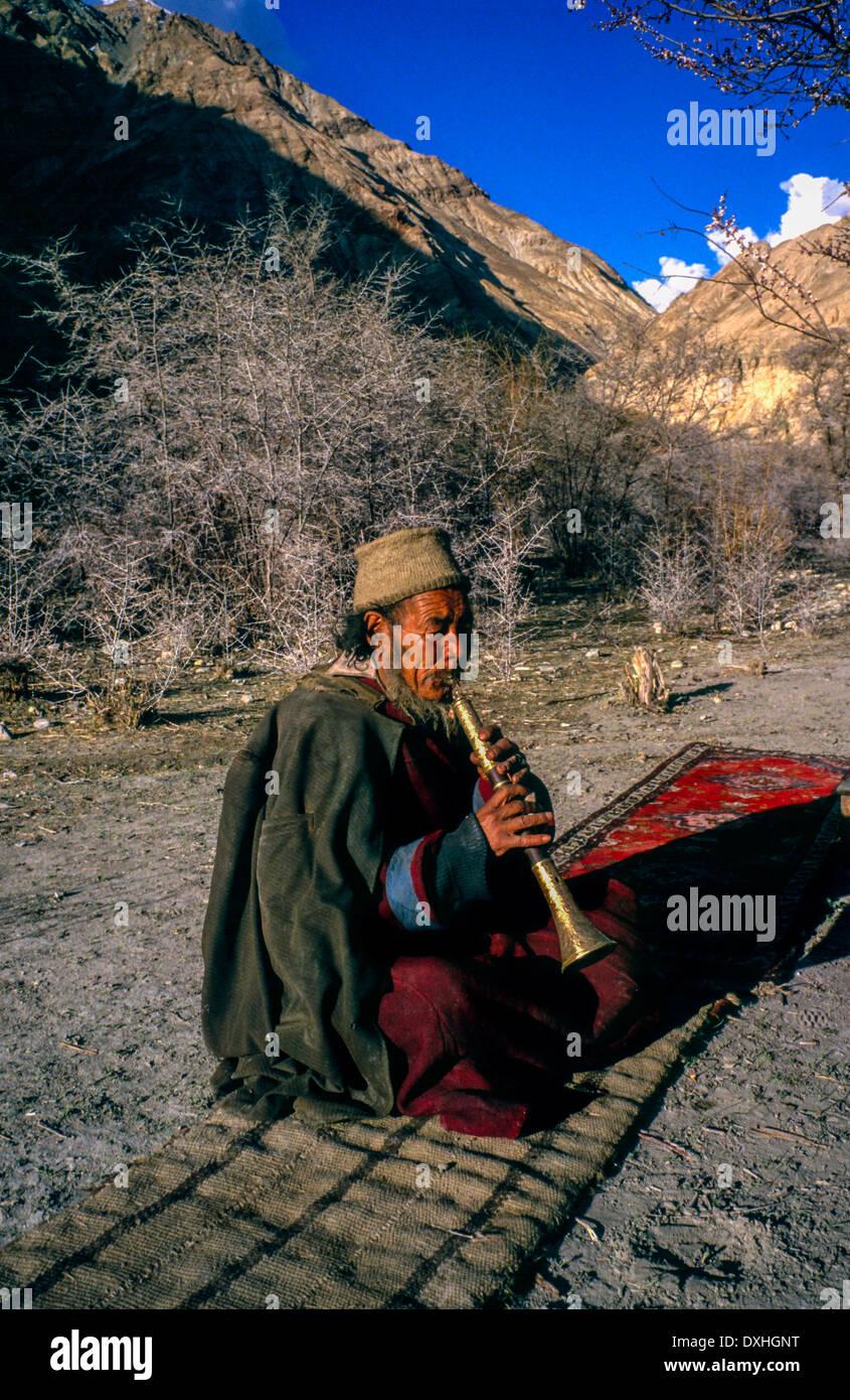 Ladakh village man sat cross legged playing brass horn clarinet carpet landscape apricot trees mountains blue sky sunshine - Stock Image