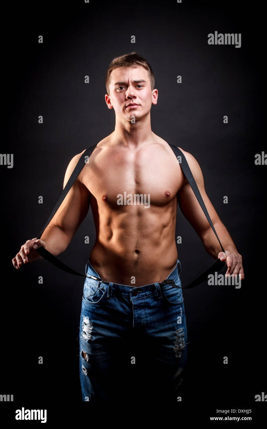 Portrait of a handsome well-built man posing in short jeans and suspenders - Stock Image