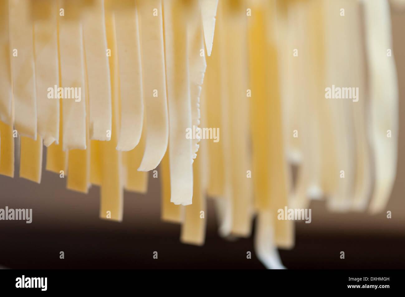 Fresh handmade Italian pasta hanging off a rack before cooking - Stock Image