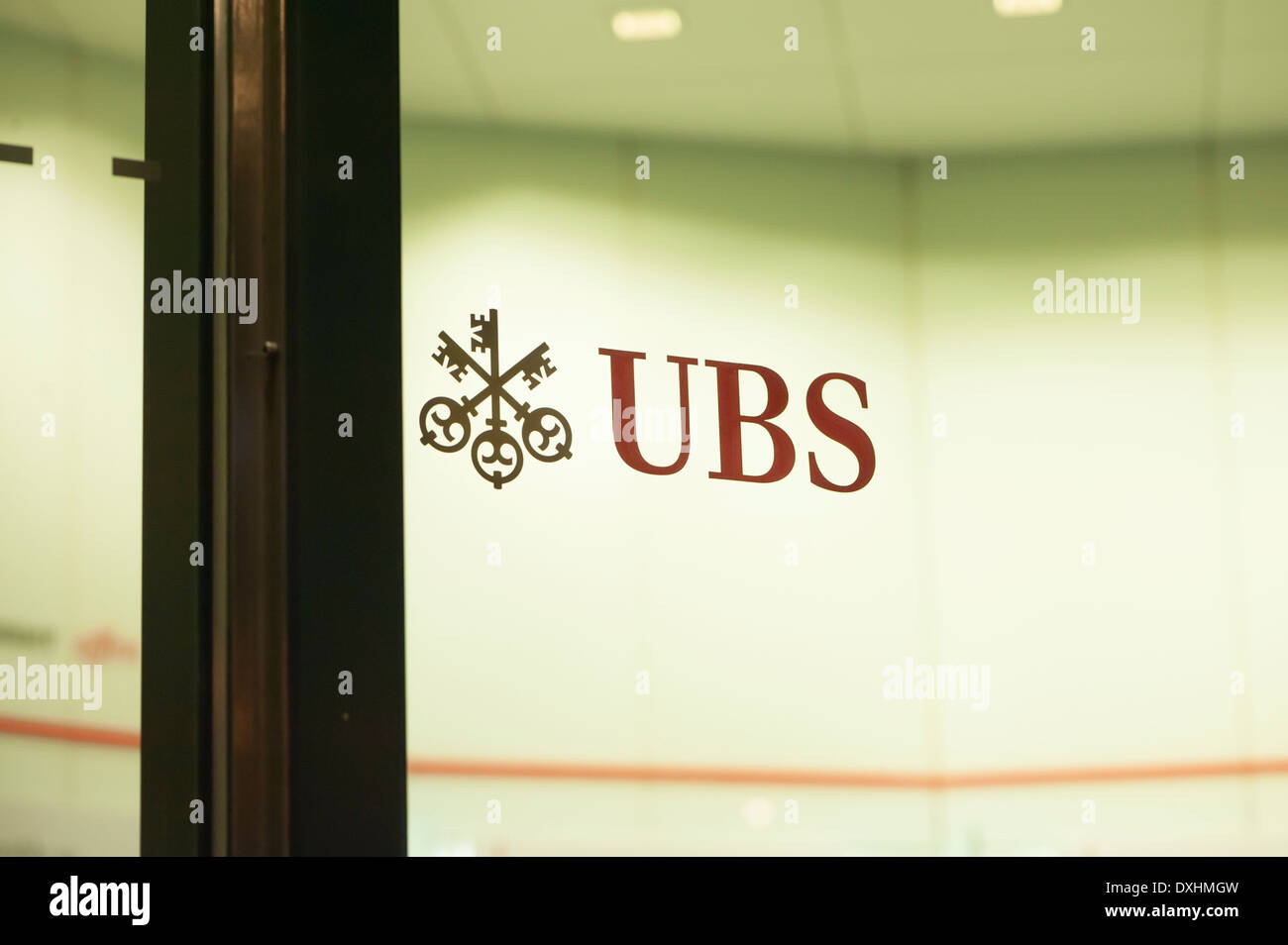 Logo of UBS, Switzerland's largest bank on the glass door of a UBS cashpoint on Bahnhofstrasse in Zurich, Switzerland, at night. - Stock Image