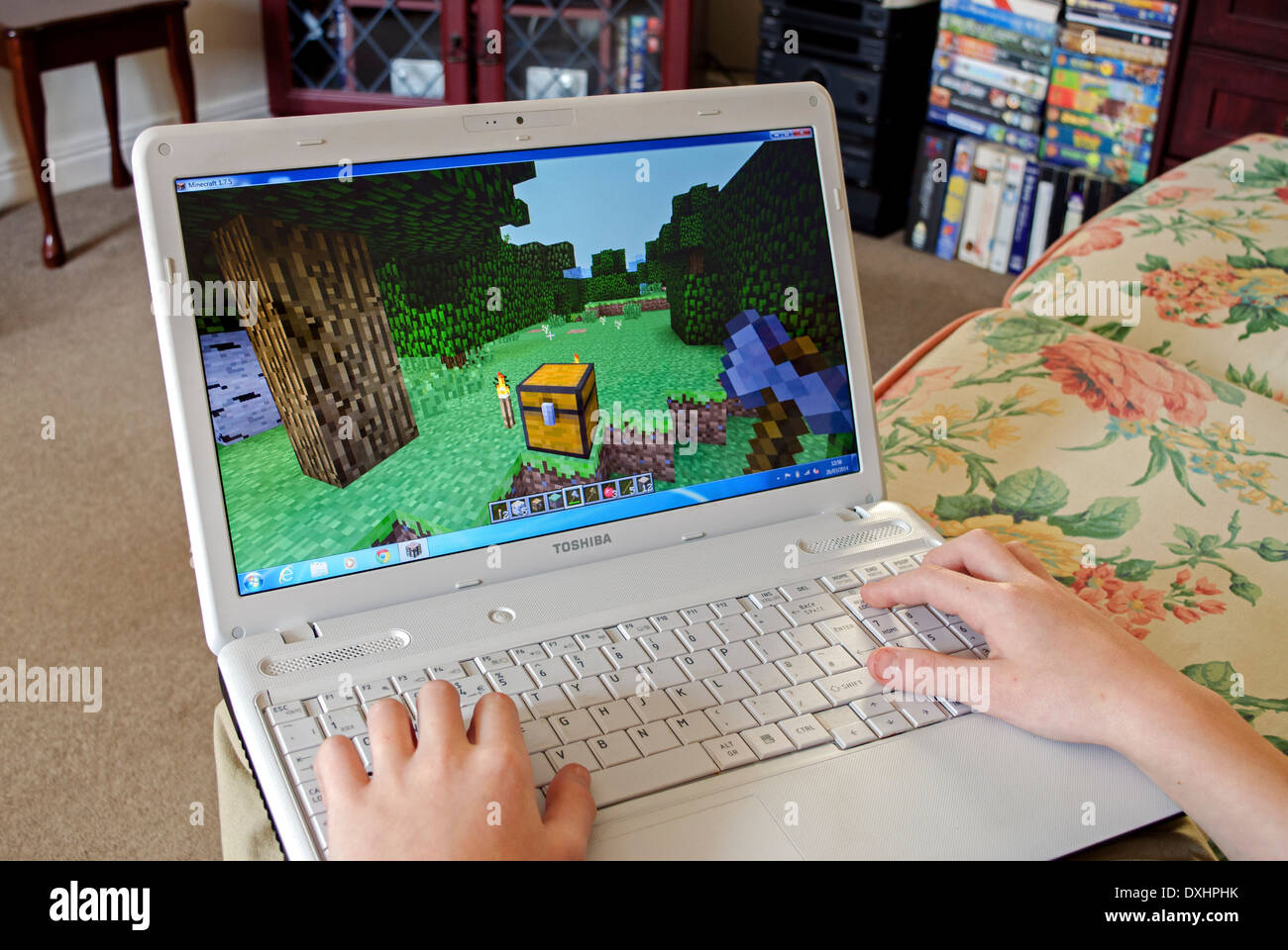 young boy playing minecraft on a laptop computer - Stock Image