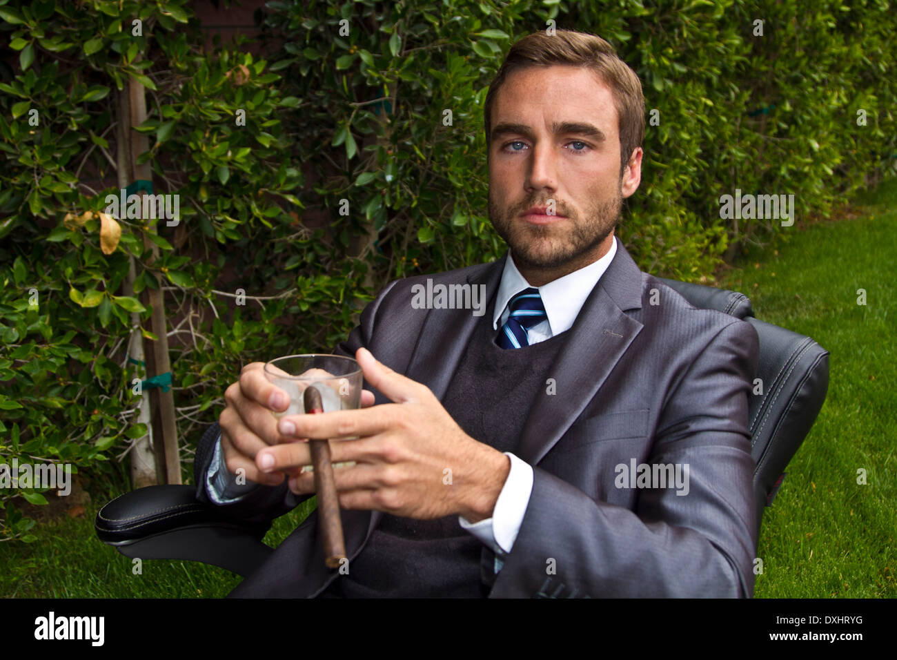 Business man outside in office chair outside - Stock Image
