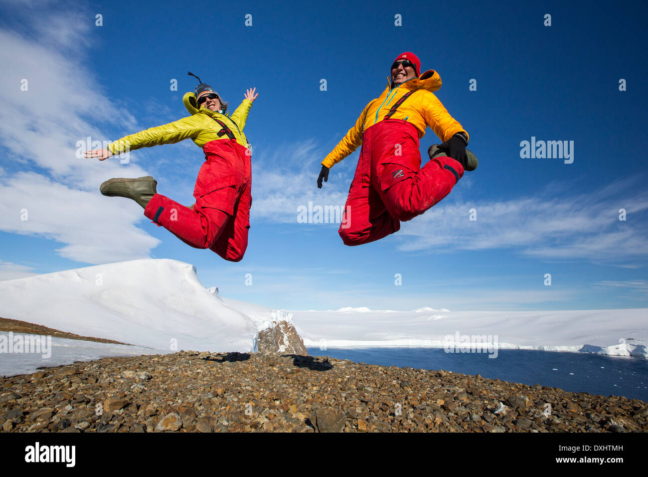 A man and woman jumping for joy from an expedition cruise on Joinville Island just off the Antarctic Peninsular. - Stock Image